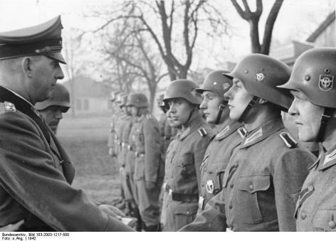 """Scherl: SS-Oberst-Gruppenführer und Generaloberst der Polizei Daluege überreicht den Offizieren und Männern des Polizei-Bataillons """"Cholm"""", die der Kampfgruppe Scherer angehörten, den vom Führer verliehenen Cholm-Schild. 7053-42"""