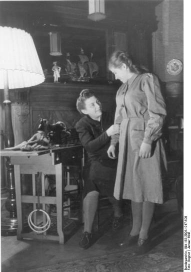 Scherl Bilderdienst: Deutschland, Januar 1945 Wie ergeht es der Ostarbeiterin Helena B. aus Kiew in Deutschland? Helena hat ein neues Kleid geschenkt bekommen. Leider ist es etwas zu groß für sie. Ihre neue Pflegemutter, deren Haushalt sie so gut besorgt, ändert es selbst und freut sich mit ihr zusammen über das schmucke, hübsche Gewand. 250-45 SS-PK Bogner
