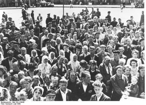 Freiwillige Ostarbeiter fahren nach Deutschland Arbeitswillige und Angehörige lauschen den Worten des Bürgermeisters. Kriegsber. Kurrasch,  30. Juli 1943 [Herausgabedatum]